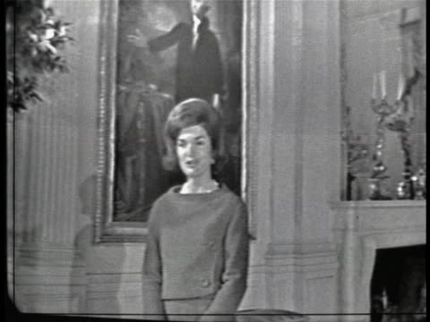 close tracking shot of jacqueline kennedy, seen from behind, as she walks through the east room of the white house. she looks back towards the camera... - jackie kennedy stock videos & royalty-free footage