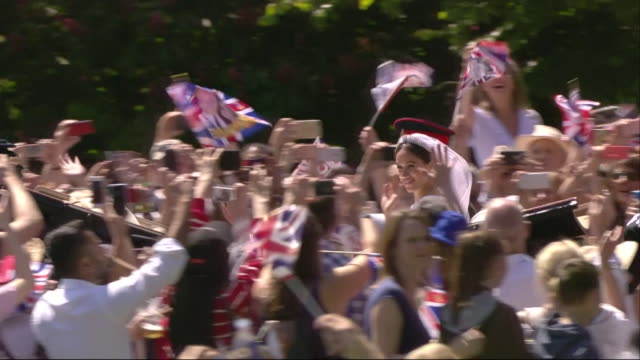 Close tracking shot showing the newlywed Duke and Duchess of Sussex over scores of cheering crowds
