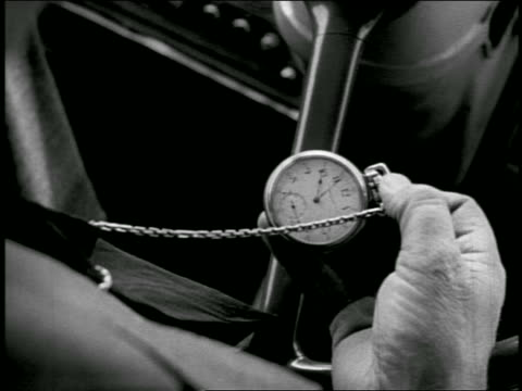 b/w close up 1940s hand of bus driver at wheel checking pocketwatch - 懐中時計点の映像素材/bロール