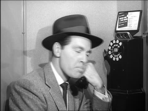 B/W close up 1957or 1958 man in hat dialing on pay phone / smiles + starts talking