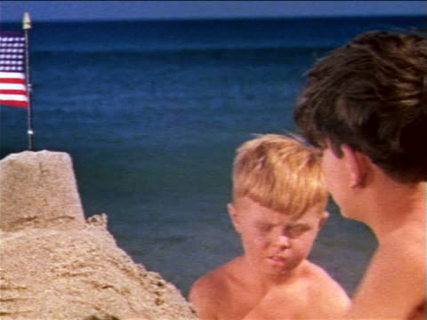 1959 close up 2 boys on beach building sand castle with American flag on top / ocean waves in BG/ industrial
