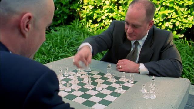 close up 2 businessmen playing chess / shaking hands - チェス点の映像素材/bロール