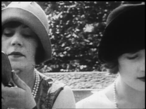 b/w 1925 close up pan 2 flappers sitting on bench putting on make up + chewing gum / newsreel - gomma da masticare video stock e b–roll