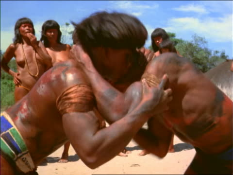 close up 2 native men wrestling / women watching in background / amazonas, brazil - grundschüler stock-videos und b-roll-filmmaterial