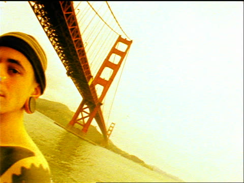 SEPIA close up PAN 2 shirtless Gen X men covered in tattoos + body piercings / Golden Gate Bridge in background