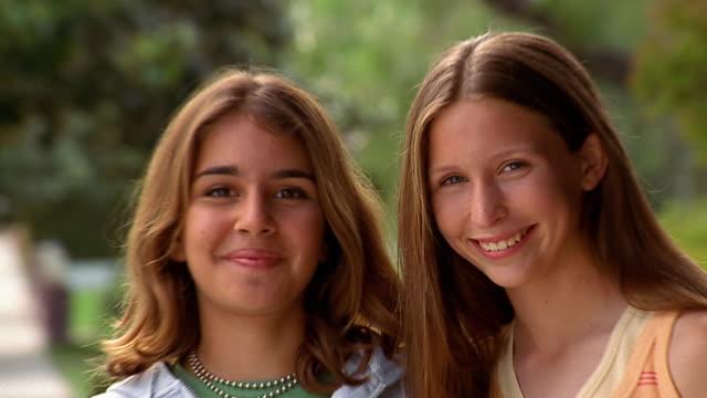 vidéos et rushes de close up 2 teenage girls posing arm in arm / tilt down tilt up girl holding skateboard - jeunes filles