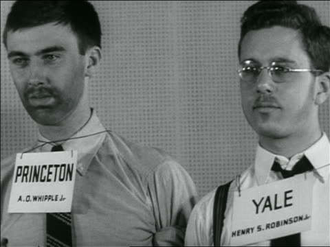 "B/W 1936 close up 2 young men with signs on necks reading ""Princeton"" + ""Yale"" / newsreel"
