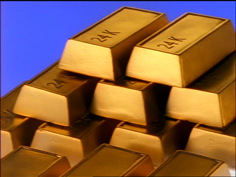 close up pan 24k gold ingots sitting in stacks / blue background - lingotto video stock e b–roll