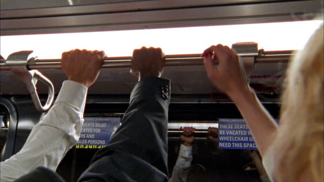 close up 3 hands grabbing railing in subway - pendler stock-videos und b-roll-filmmaterial