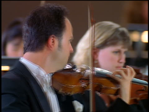 close up pan 3 violinists playing in orchestra - violin stock videos & royalty-free footage