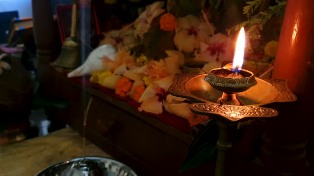 close up a brass stand with burning diya / oil lamp with fire/ flame and defocused flowers, conch shell, holly book, smoke of incense stick at the background- 4k stock footage - conch stock videos & royalty-free footage
