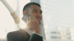 Close up a businessman in a black suit using his smartphone talking on the phone while standing outside on the street near a big office building urban having sunlight sunset.
