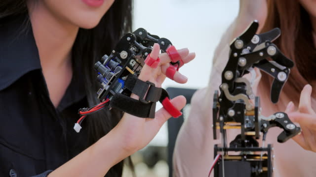 close up a futuristic prosthetic robot arm by a teenage girl having fun of development engineer in a research laboratory.arm moves its fingers.industry 4.0.education,technology,teamwork,science and people concept. - medical equipment stock videos & royalty-free footage