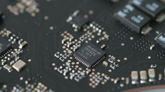 Close up a Maxim Integrated Products Inc integrated circuit chip from a stripped Apple Inc MacBook Pro laptop computer is arranged for video shot in...