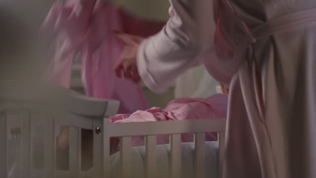 close up - a mother in a pink robe changes the diaper of baby in a white nursery. - baby blanket stock videos and b-roll footage