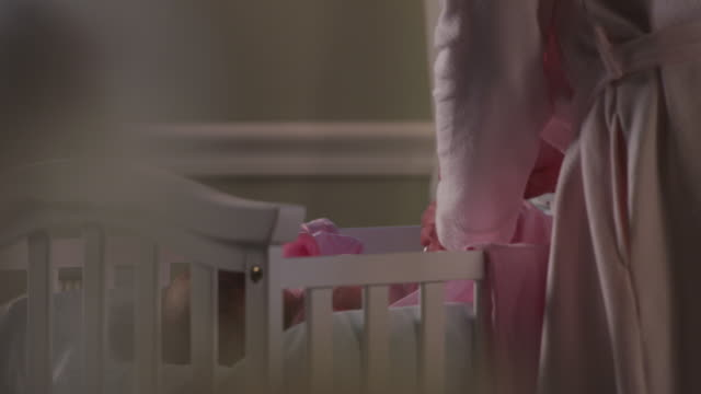 close up - a mother in a pink robe swaddles her baby in a pink blanket after changing the diaper in a white nursery. - baby blanket stock videos and b-roll footage