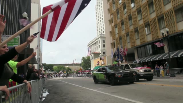 close up a parade spectators is waving a usa flag to honor veterans of the vietnam war the bay of pigs and all wars the city of miami holds the... - miami dade county bildbanksvideor och videomaterial från bakom kulisserna