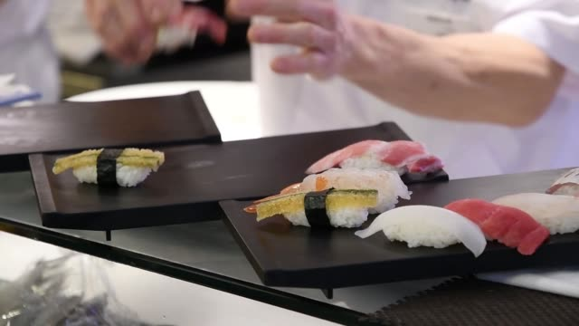 close up a plate of sushi sits at a sushi zanmai sushi restaurant operated by kiyomura kk in tokyo japan on friday jan 5 a sushi chef prepares plates... - sushi video stock e b–roll