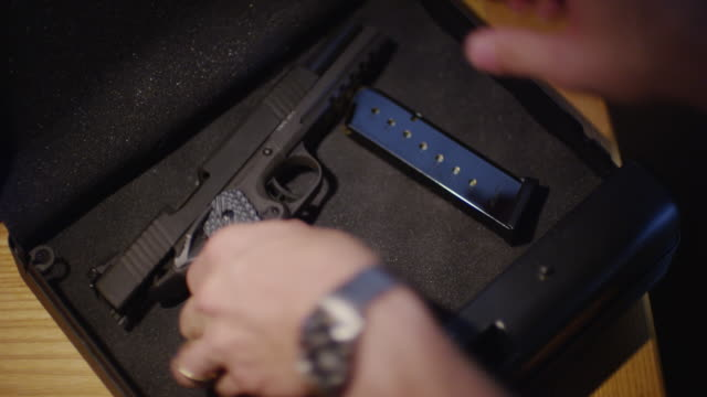 close up a semi-automatic pistol and ammunition clip are placed in a locked case for safety. - aktentasche stock-videos und b-roll-filmmaterial