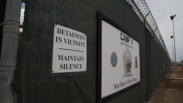 close up, a sign reading, 'detainees in vicinity maintain silence', is seen on the security wall around camp v where prisoners are housed in a single... - guantanamo bay stock videos & royalty-free footage