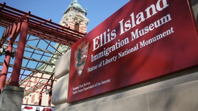 vídeos de stock e filmes b-roll de ellis island immigration museum statue of liberty national monument tourists visit the ellis island immigration museum after it was reopened to the... - emigração e imigração