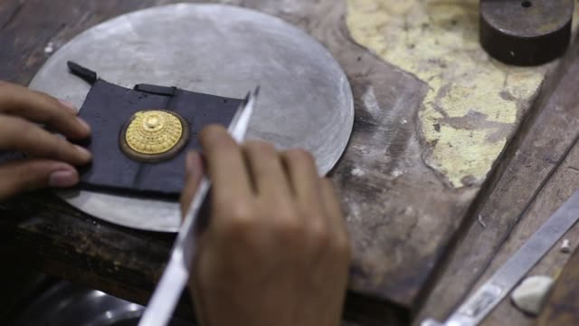 Close up a worker labors on a piece of gold jewelry at a PN Gadgil Jewellers Pvt workshop in Pune India on Monday Aug 17 2017