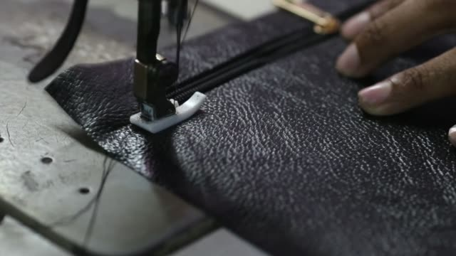 vídeos y material grabado en eventos de stock de close up, a worker uses a sewing machine while manufacturing a wallet at a leather workshop in the dharavi area of mumbai, india, on tuesday, july 18... - iva