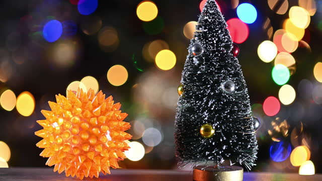 close up a yellow pointy ball that could represent a coronavirus close to a miniature christmas tree. christmas lights in the background. pan camera movement. - nadel pflanzenbestandteile stock-videos und b-roll-filmmaterial