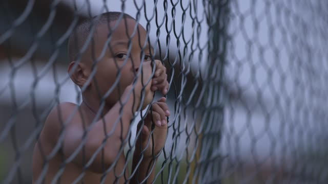 Close Up a young boy standing behind a fence and watching the football training session Youngsters train and play football in Vila Alianca Rio de...