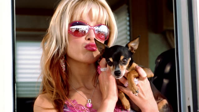 Close up actress posing with dog looking at CAM and blowing kisses