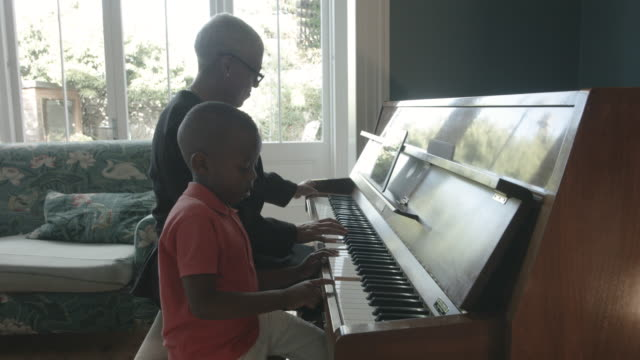 vídeos de stock, filmes e b-roll de close up, african american boy and grandmother play piano - despreocupado