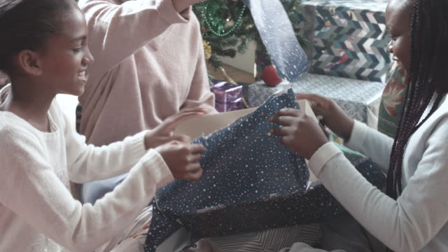 close up, african american children open gifts on christmas - christmas gift stock videos & royalty-free footage