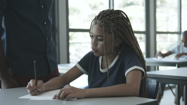close up, african american college student writes at desk - penna bildbanksvideor och videomaterial från bakom kulisserna