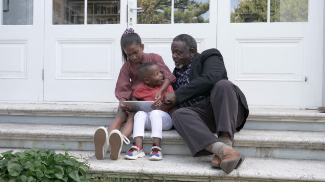 vidéos et rushes de close up, african american family look at tablet - s'appuyant