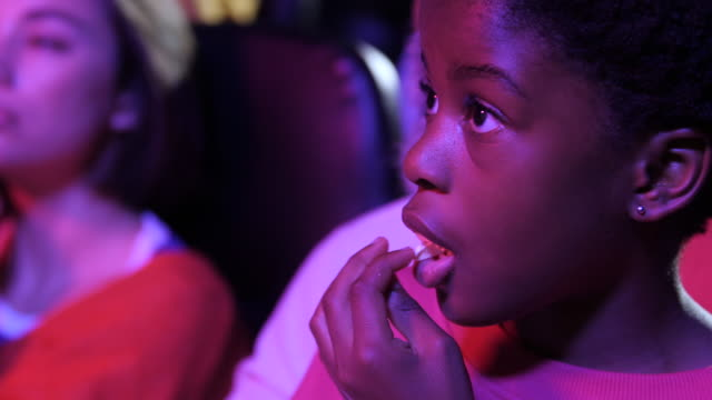 close up, african american girl eats popcorn in movie theatre - film industry stock videos & royalty-free footage