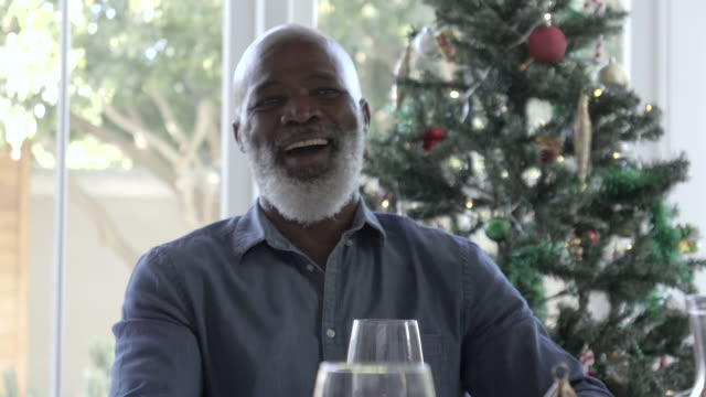 close up, african american man laughs in front of christmas tree - balding stock videos & royalty-free footage