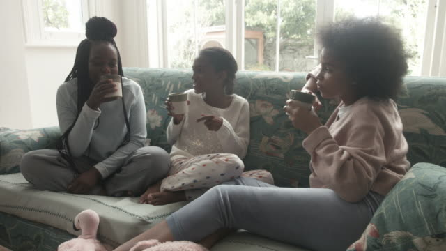 close up, african american teenagers drink hot chocolate on couch - social gathering stock videos & royalty-free footage