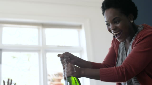 close up, african american woman pops champagne bottle - short hair stock videos & royalty-free footage