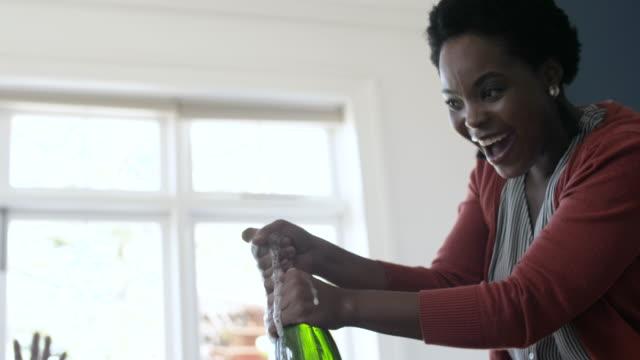 vídeos y material grabado en eventos de stock de close up, african american woman pops champagne bottle - derramar actividad