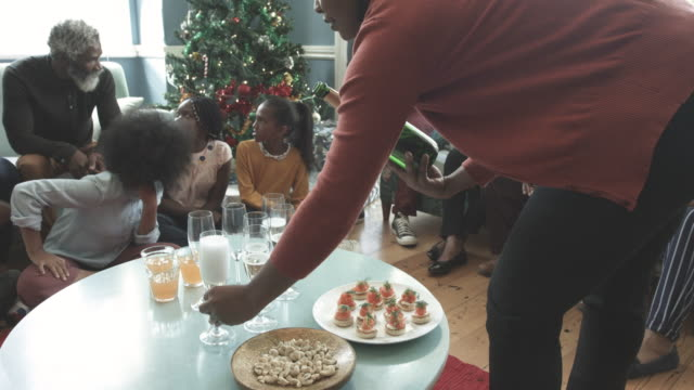 close up, african american woman pours champagne for family on christmas - drink bildbanksvideor och videomaterial från bakom kulisserna