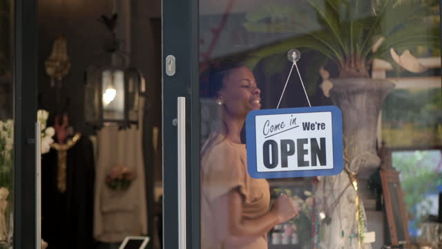 close up african woman turns open sign on store window - store sign stock videos & royalty-free footage