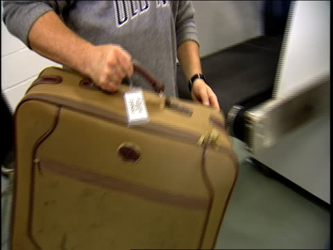 Close up airport security screeners taking suitcase from x-ray machine, opening it, and finding two knives