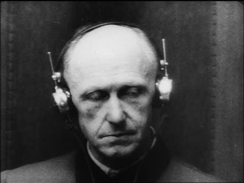 b/w 1945/46 close up alfred jodl listening on headphones at war crime trials / nuremberg / documentary - processi di norimberga video stock e b–roll