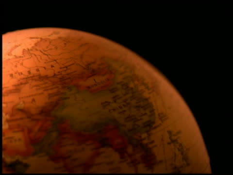 stockvideo's en b-roll-footage met close up amber globe turning against black background - bureauglobe