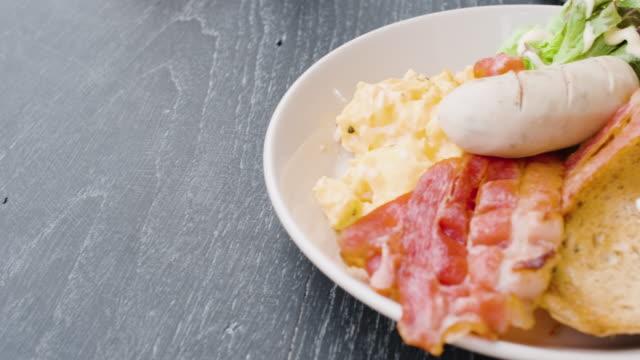 vídeos y material grabado en eventos de stock de desayuno americano de cerca en la mesa negra en la mañana al aire libre en casa.panning shot - huevos fritos de un solo lado