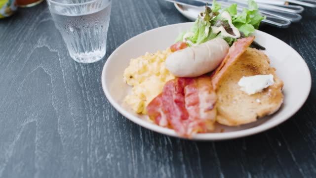 vídeos y material grabado en eventos de stock de desayuno americano de cerca en la mesa negra en la mañana al aire libre en casa.panto tiro - huevos fritos de un solo lado