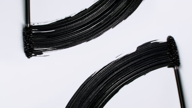 close up and slow motion of 2 black mascara swooshes side by side created with 2 mascara wands on white background - メイクアップブラシ点の映像素材/bロール