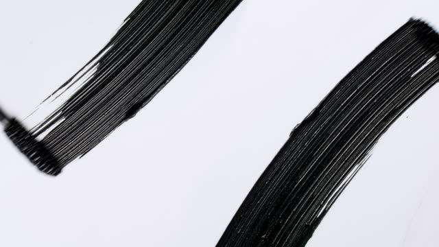 close up and slow motion of 2 black mascara swooshes side by side created with 2 mascara wands on white background - symbol stock videos & royalty-free footage