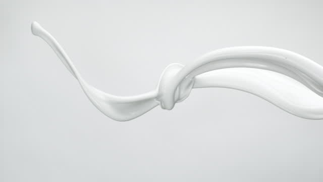 close up and slow motion of 2 liquid milk streams flowing and throwing in air with splashes against a light grey background - moving down stock videos & royalty-free footage