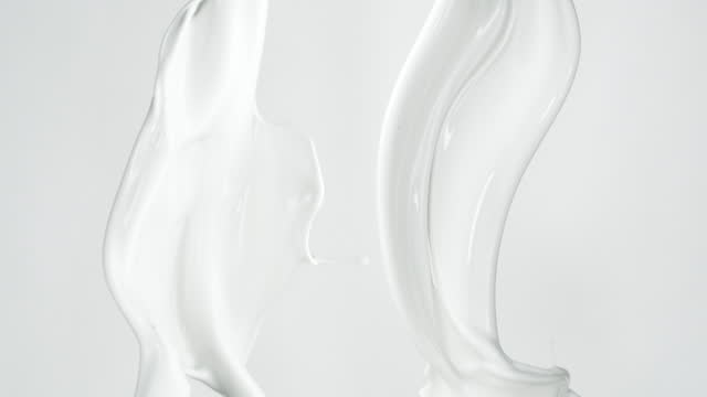 close up and slow motion of 2 milk liquid streams pouring from the top and falling down with splashing against a light grey background - pouring stock videos & royalty-free footage